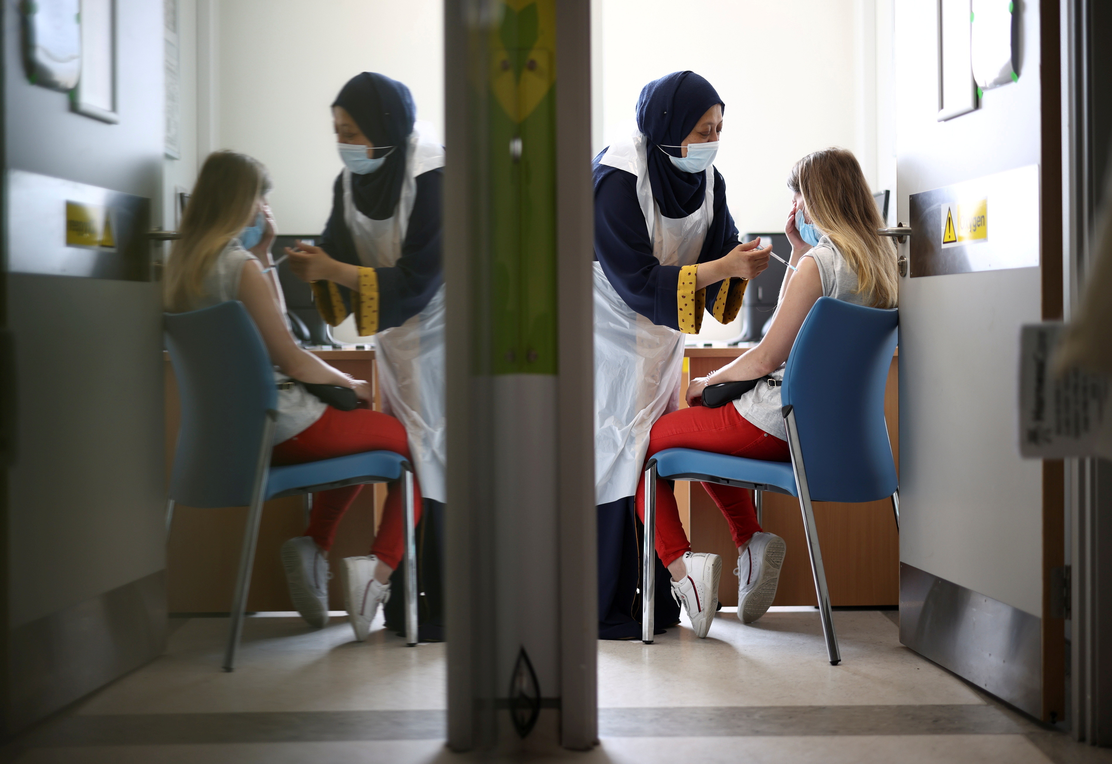 ▲▼英國倫敦一名女性正在接種輝瑞BNT疫苗。(圖/路透社)