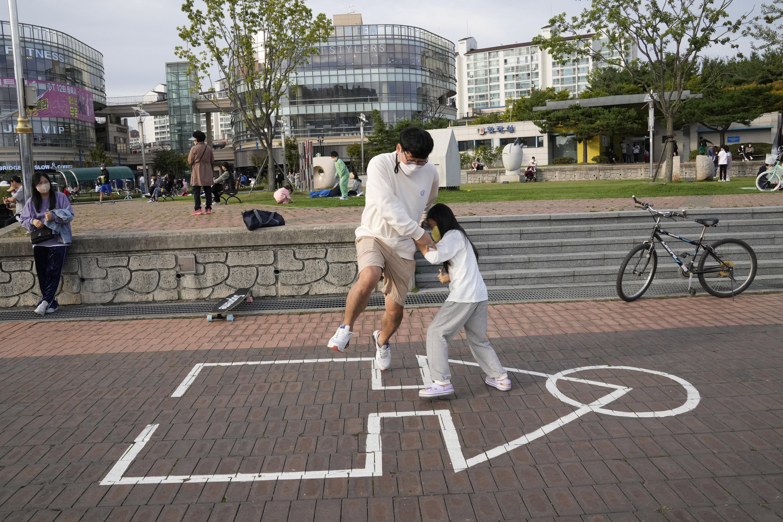 ▲▼南韓一對父女在京畿道高陽市某公園玩魷魚遊戲。(圖/達志影像/美聯社)