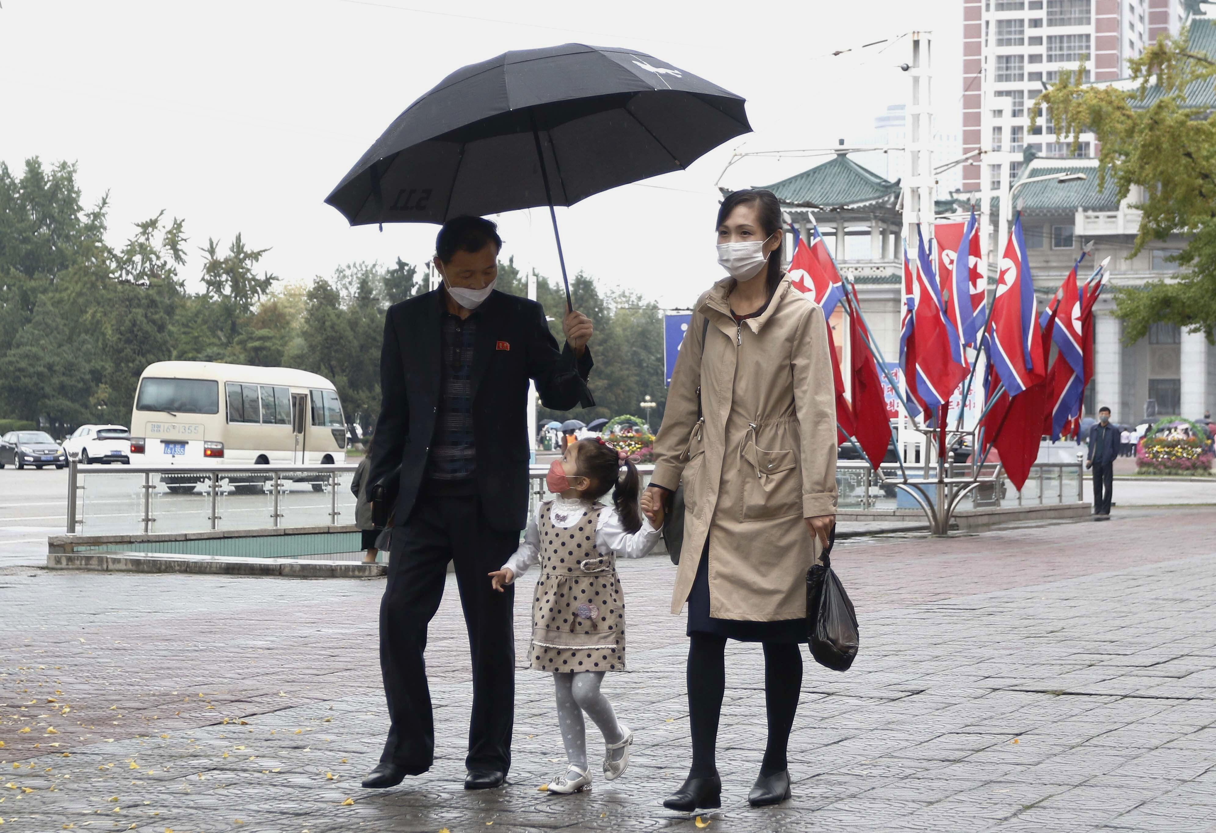 ▲▼北韓雙十黨慶當天,一名女孩牽著父母漫步在掛滿國旗的平壤街頭。(圖/達志影像/美聯社)