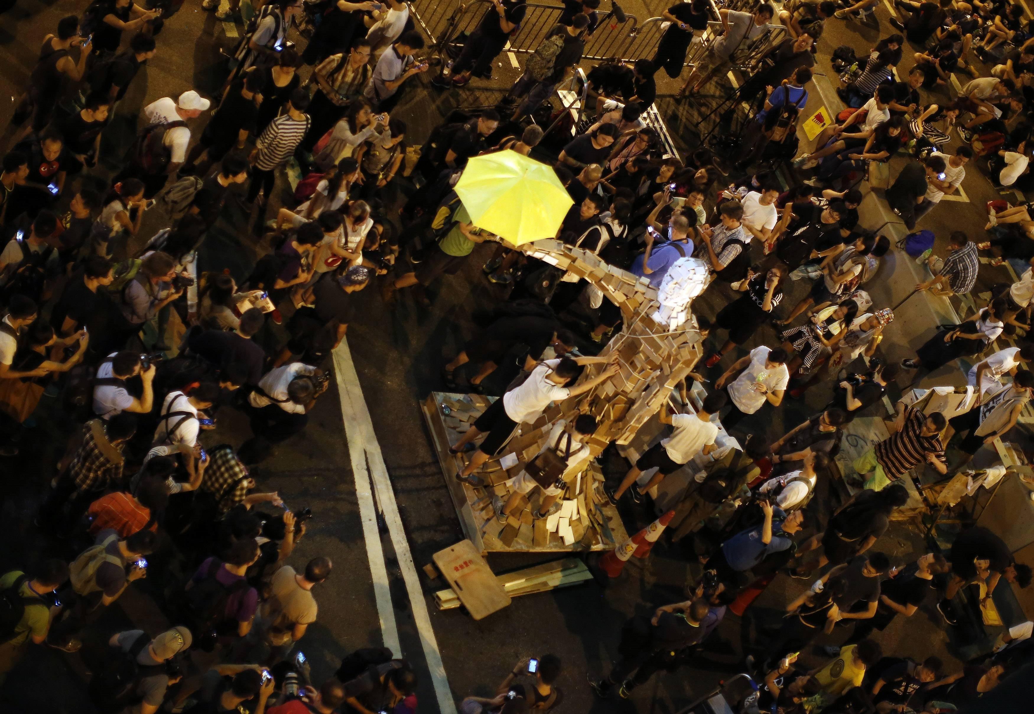 撐起黃色雨傘,佔中群眾不退散。(圖/路透社)